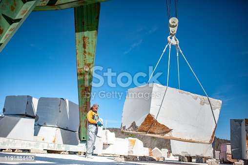 Adult Man Working With Crane For Transporting Block Shape Marble.