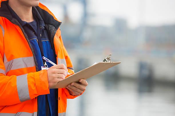adult man writing on clipboard in shipping yard stock photo