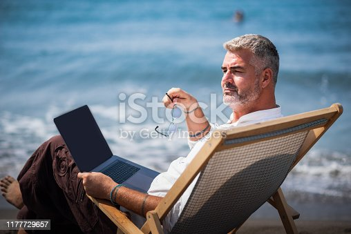 istock Adult mature man working on his laptop next to the beach 1177729657