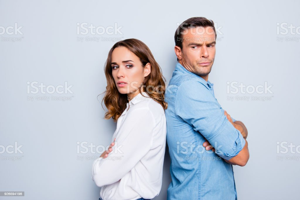 Adult mature sad, upset couple in shirts, casual outfit having family conflict, standing back to back with crossed arms ignoring each other over grey background stock photo