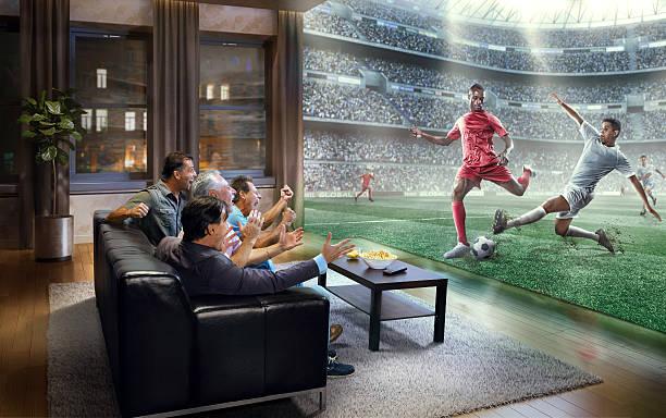 adult men are watching very realistic soccer game on tv - fußball themenzimmer stock-fotos und bilder