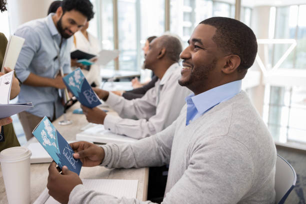 Adult men hand out information at a conference At a conference for university students, doctors hand out information about medical advances in foreign countries. college fair stock pictures, royalty-free photos & images