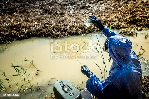 An ecologist men who taking a sample of waste water for chemistry analyse.