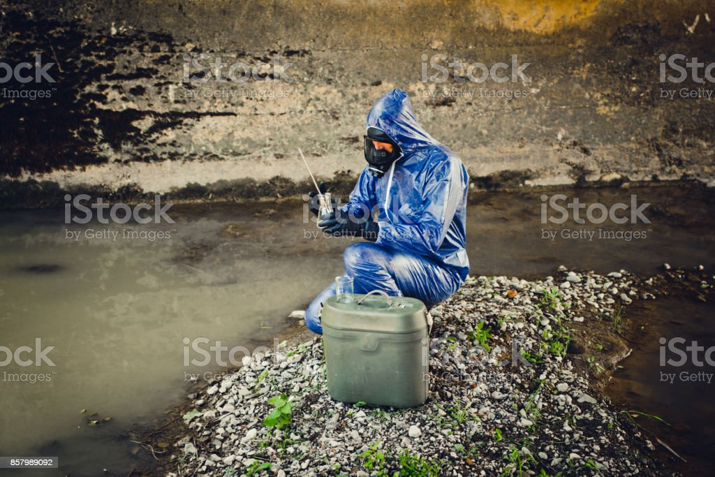 Adult Men Taking a Scientific Sample of Waste Water stock photo
