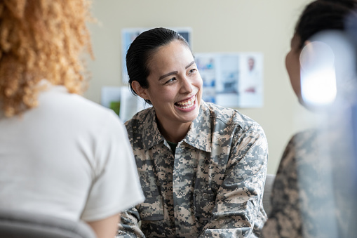 Adult military woman smiling during group therapy discussion