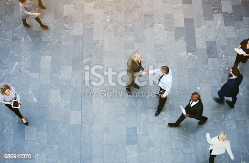 istock Adult office workers shaking hands in crowded hall 686942370