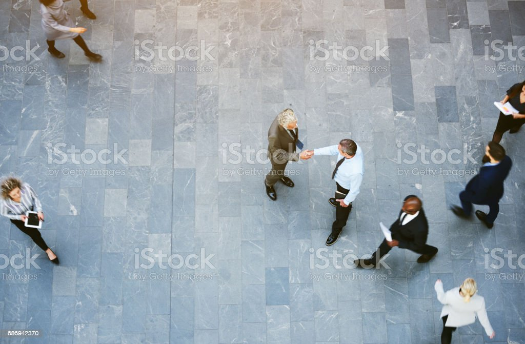 Adult office workers shaking hands in crowded hall stock photo