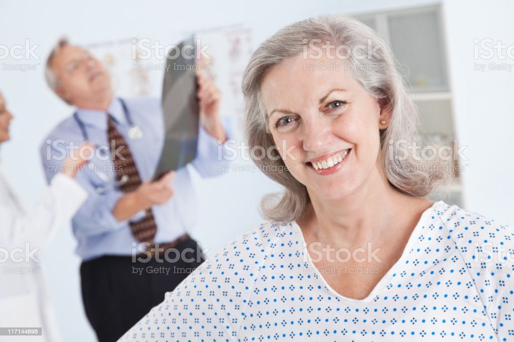 Adult Patient in Doctor's Office While Doctors Look at X-Ray royalty-free stock photo
