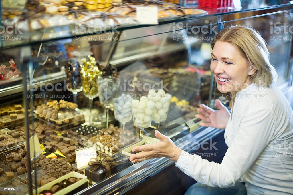 Adult pensioner buying chocolate foto royalty-free