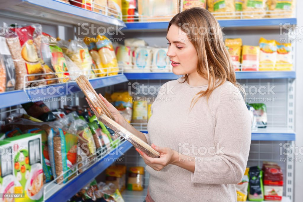 Adult positive woman buyer with  cake layers of grocery food store - Royalty-free 30-34 Years Stock Photo