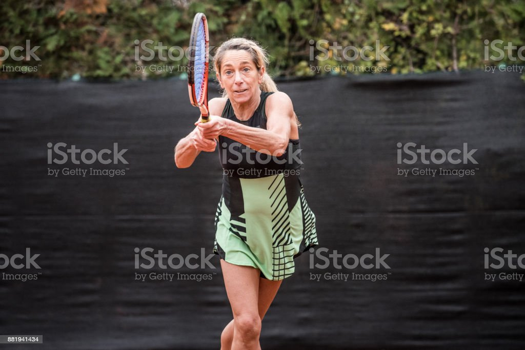 Adult Recreational Tennis Player Holding a Racket with Both Hands stock photo