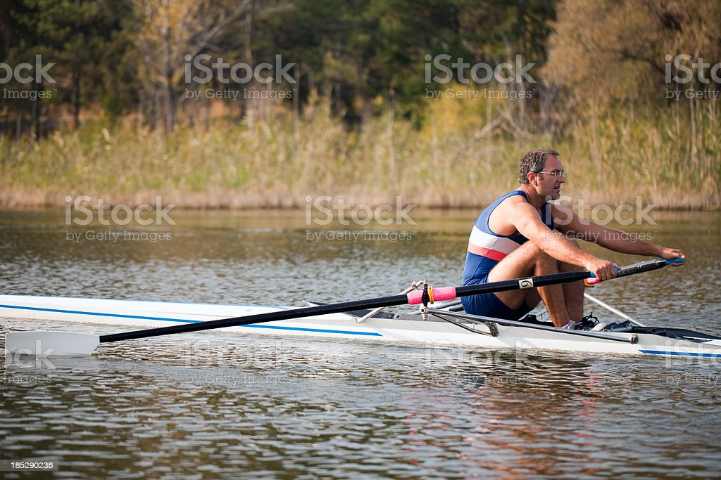 Adult Rower man rowing sculling boat on lake royalty-free stock photo