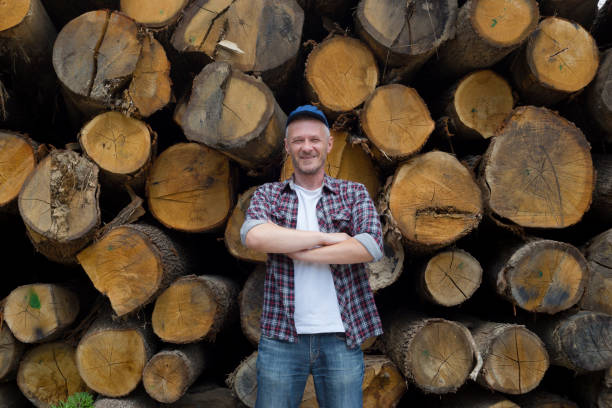 Adult satisfied lumberjack standing in front of large pile of timber Photo is taken with full frame dslr camera outdoors forester stock pictures, royalty-free photos & images