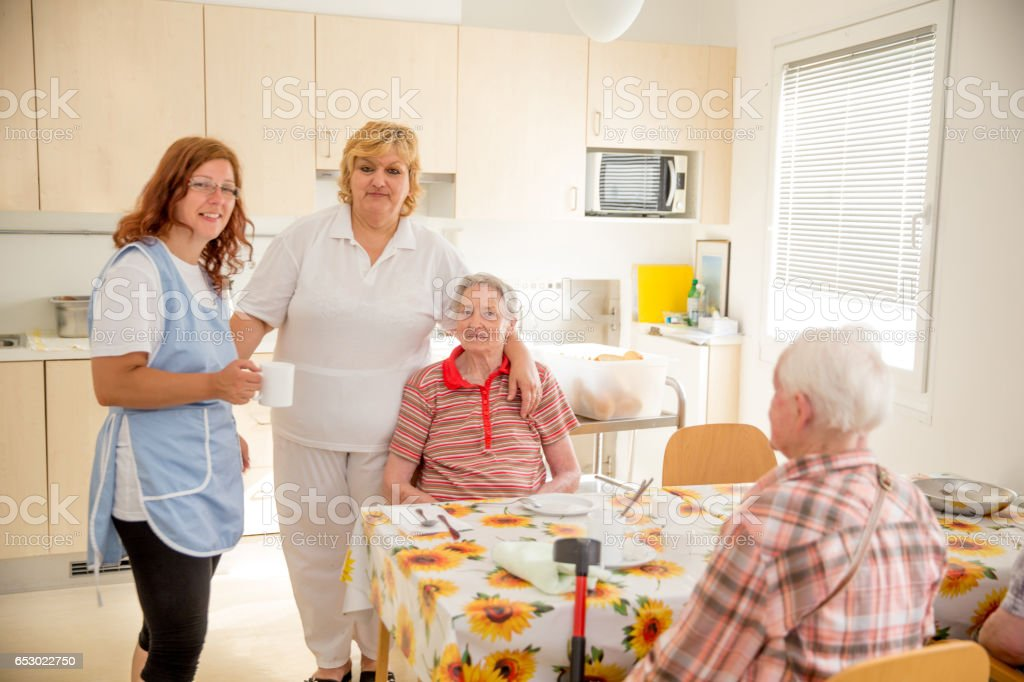 Adult Senior Socializing In The Dining Room Of The Care Center stock photo