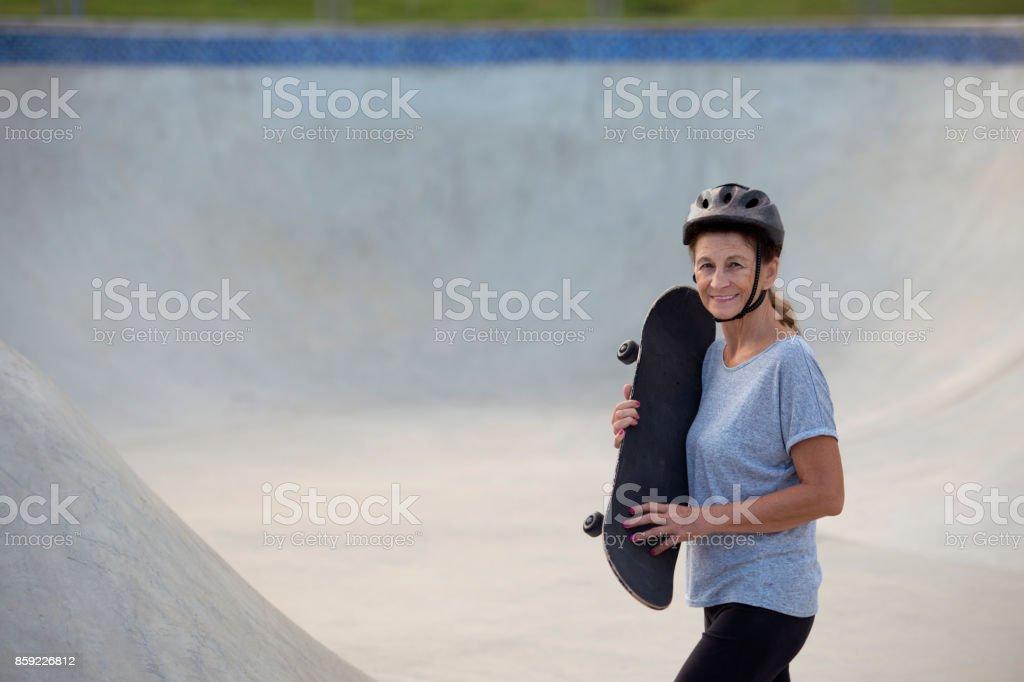 Adulta mulher sênior aprendendo alguma coisa nova - passeio no skate. - foto de acervo
