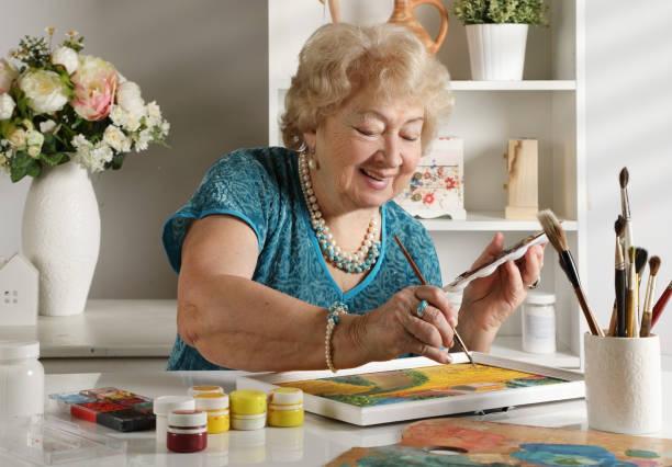 Mujer adulta de edad que pinta un cuadro en su estudio - foto de stock