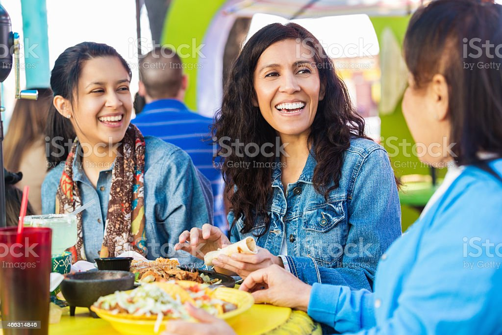 Adult sisters having lunch with mother outdoors at Mexican restaurant stock photo