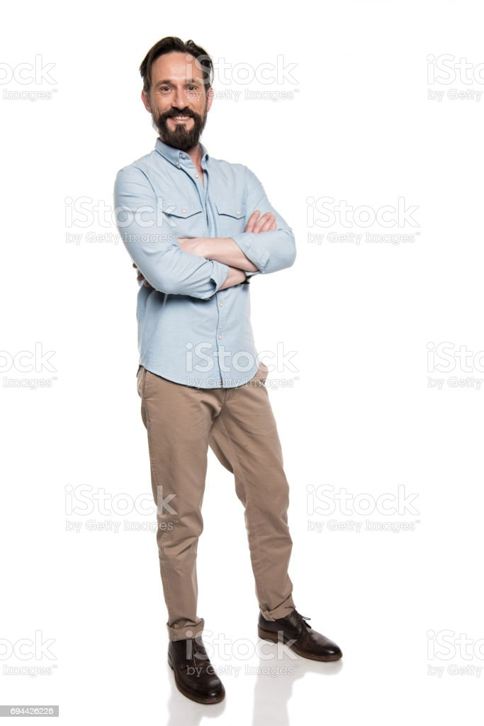 adult smiling man in casual clothes standing with crossed arms and looking at camera isolated on white stock photo