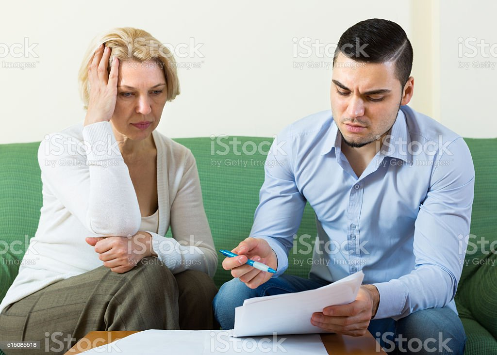 Adult son and senior mother with papers stock photo