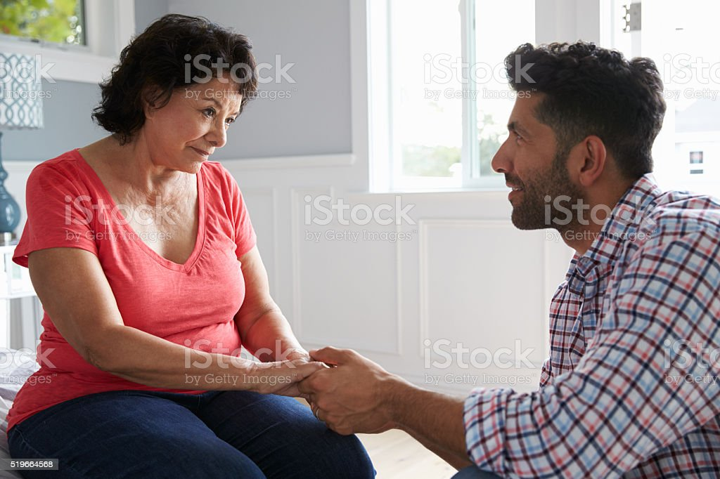 Adult Son Comforting Mother Suffering With Dementia stock photo