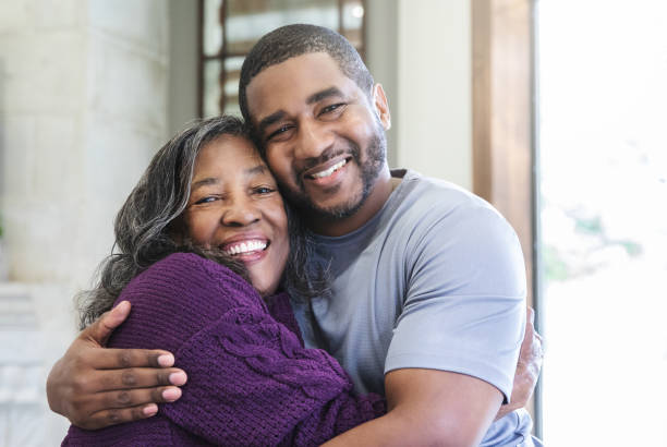 Adult son embracing senior mother stock photo