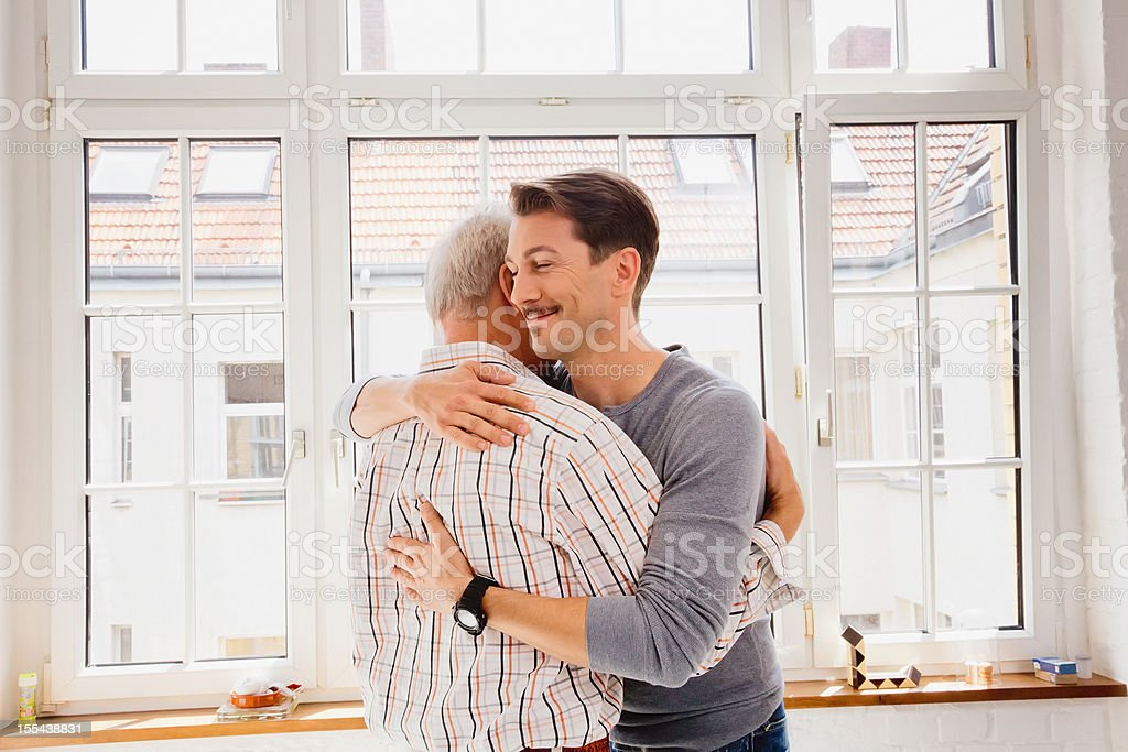 Adult son hugging his dad stock photo