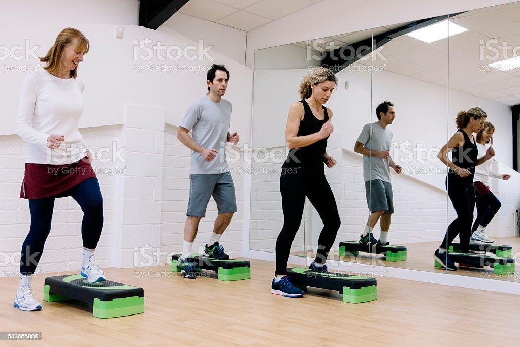 Adulto Etapa aula de aeróbica em uma academia de ginástica - foto de acervo