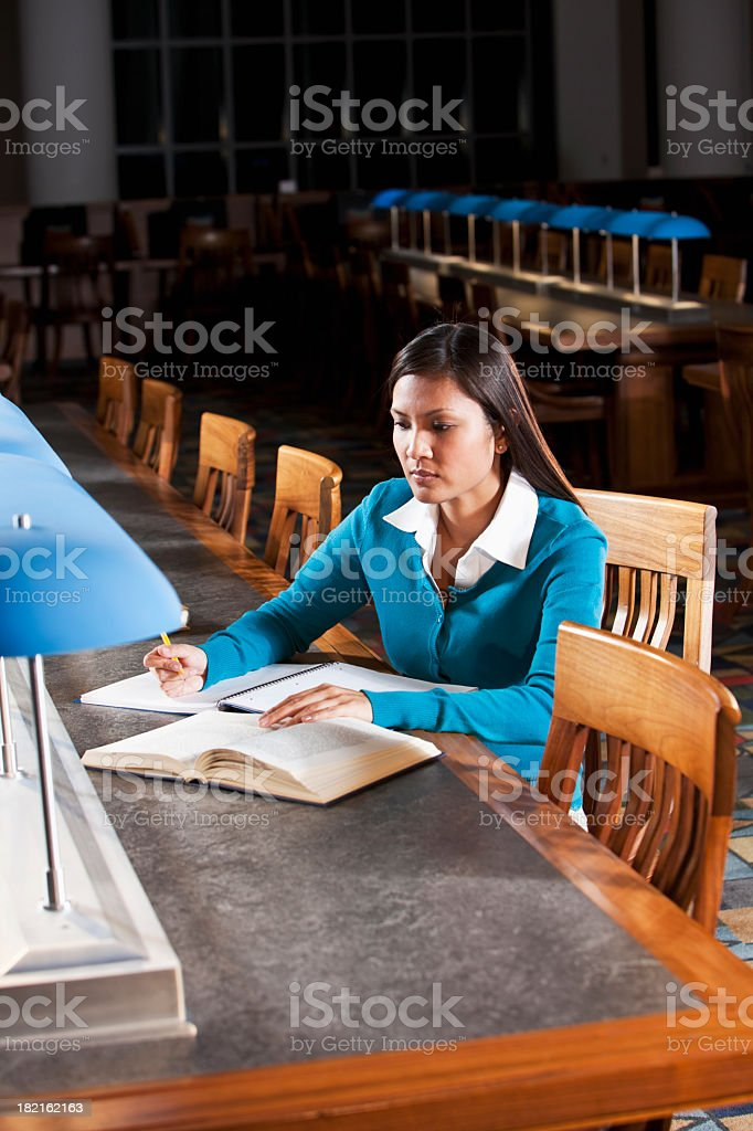 Adult student doing homework in library stock photo