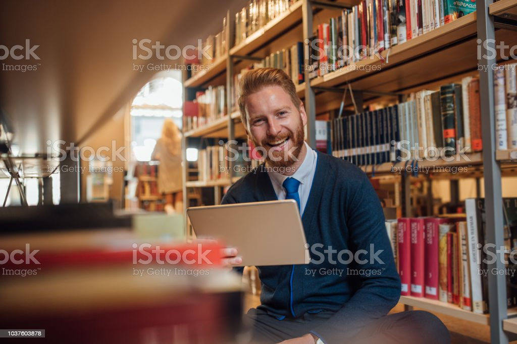 Young man sitting in the library and reading from digital tablet
