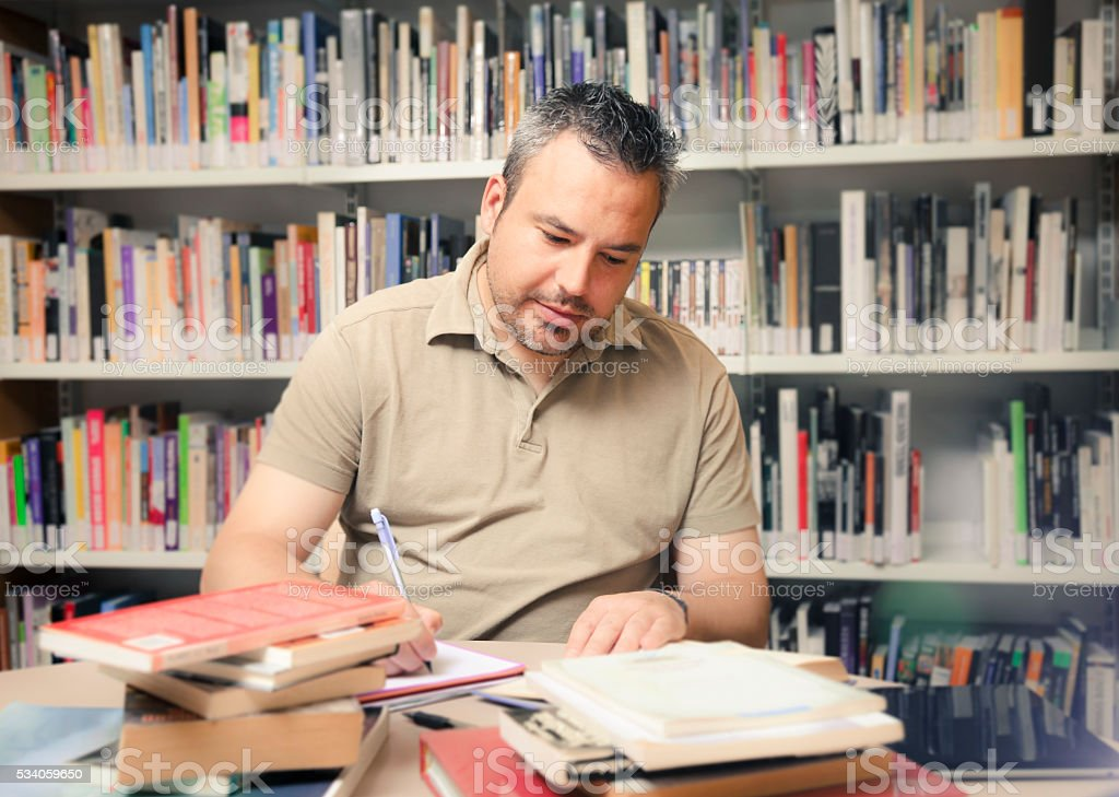 Adult student or teacher in a public library stock photo