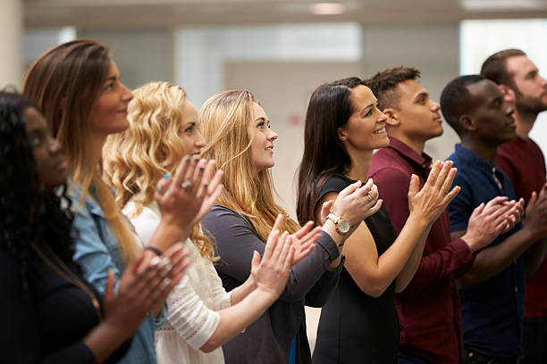 adult students applauding at an event in their university - audience clapping stock photos and pictures
