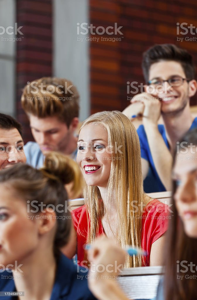 Adult students at the university Adult students sitting in the lecture hall at the university and listening to the lecture. Focus on the smiling young woman. 20-24 Years Stock Photo