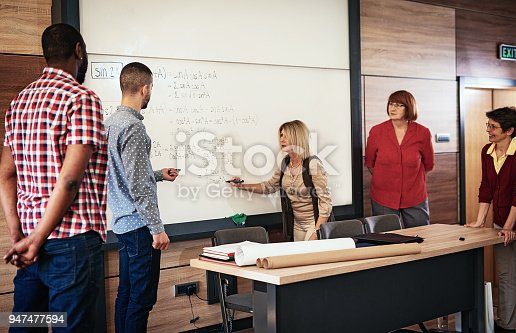 956725740istockphoto Adult students in lecture hall learning mathematics 947477594