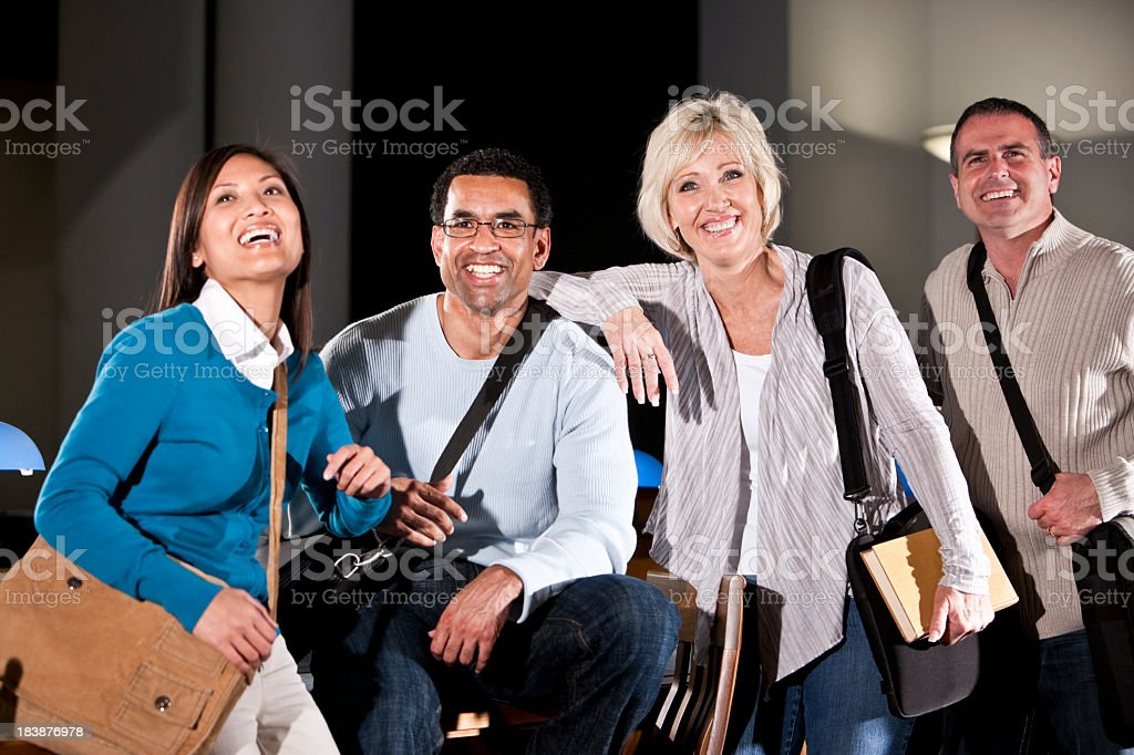 Adult students standing together in library stock photo