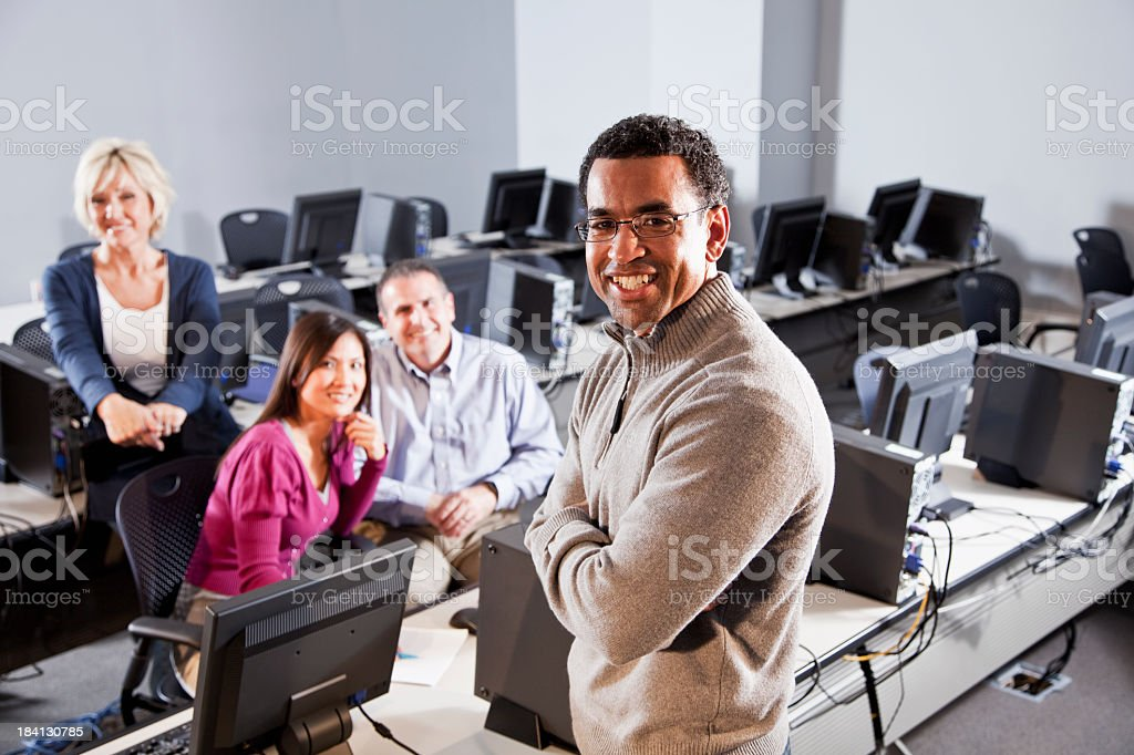 Adult students with instructor in computer lab stock photo