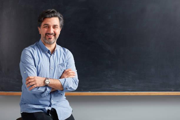 Erwachsenen Lehrer posiert auf Tafel. – Foto