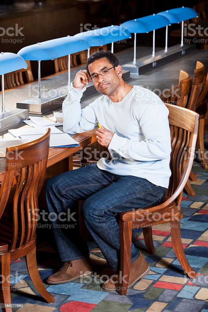 Adult university student studying in library stock photo