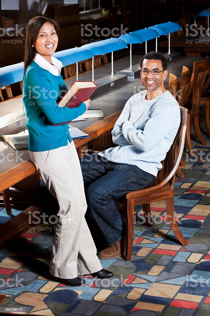 Adult university students talking in library stock photo