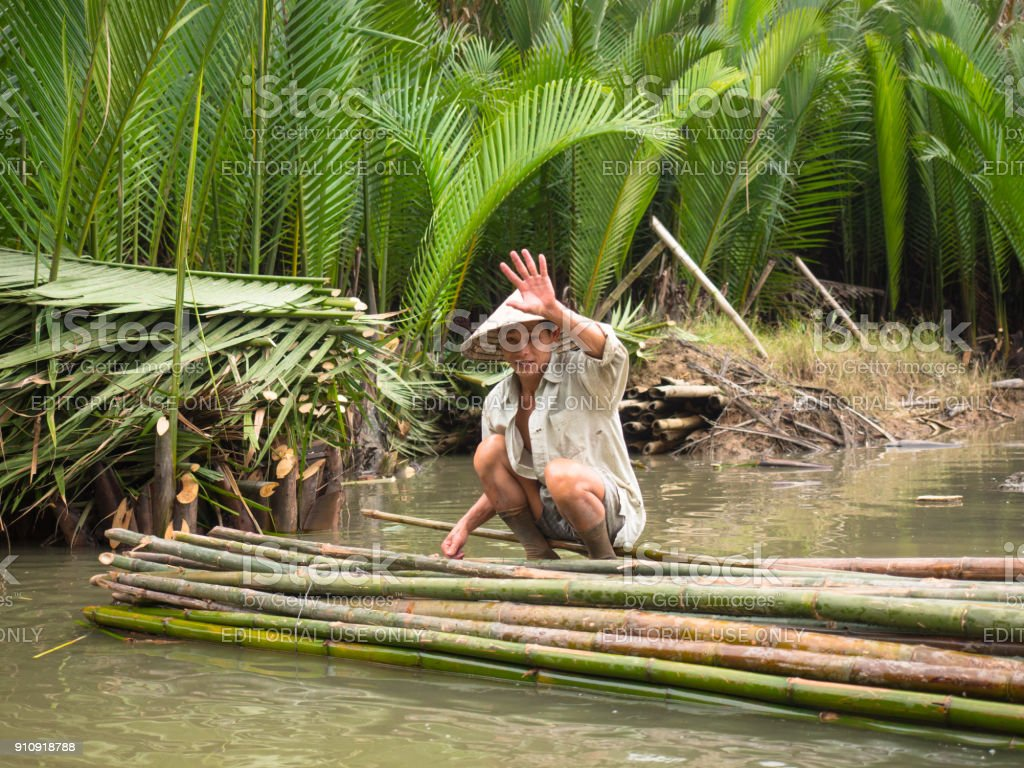 Adult Vietnamese man in traditional clothes and a conical hat is sitting on a bamboo raft and waving his hand stock photo