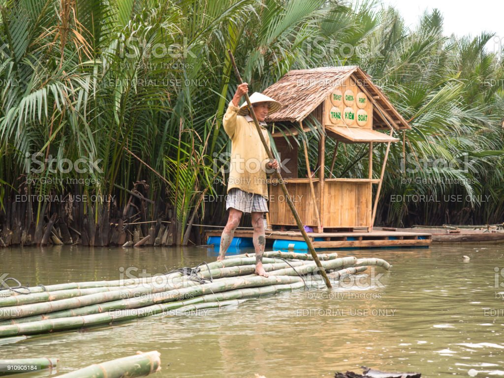 : Adult Vietnamese man in traditional clothes and a conical hat stands on a bamboo raft and is pushed by a pole from the bottom of the river stock photo