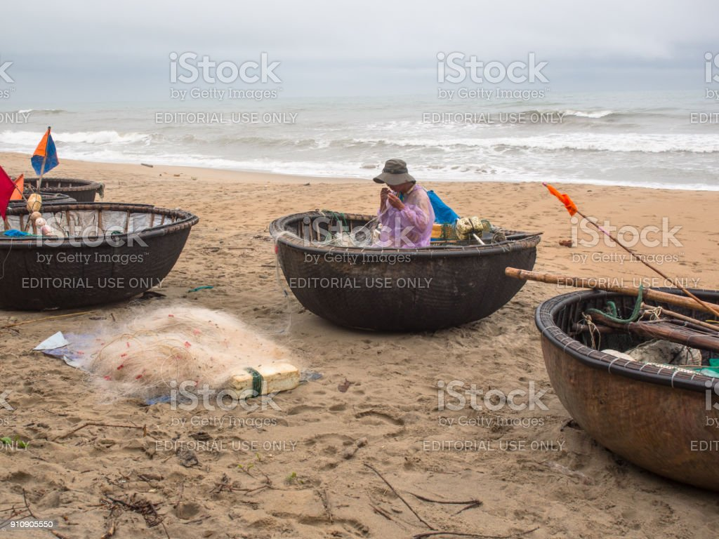 Adult Vietnamese man in traditional clothes is standing on a bamboo raft and repairing a fishing net against the background of the South China Sea stock photo