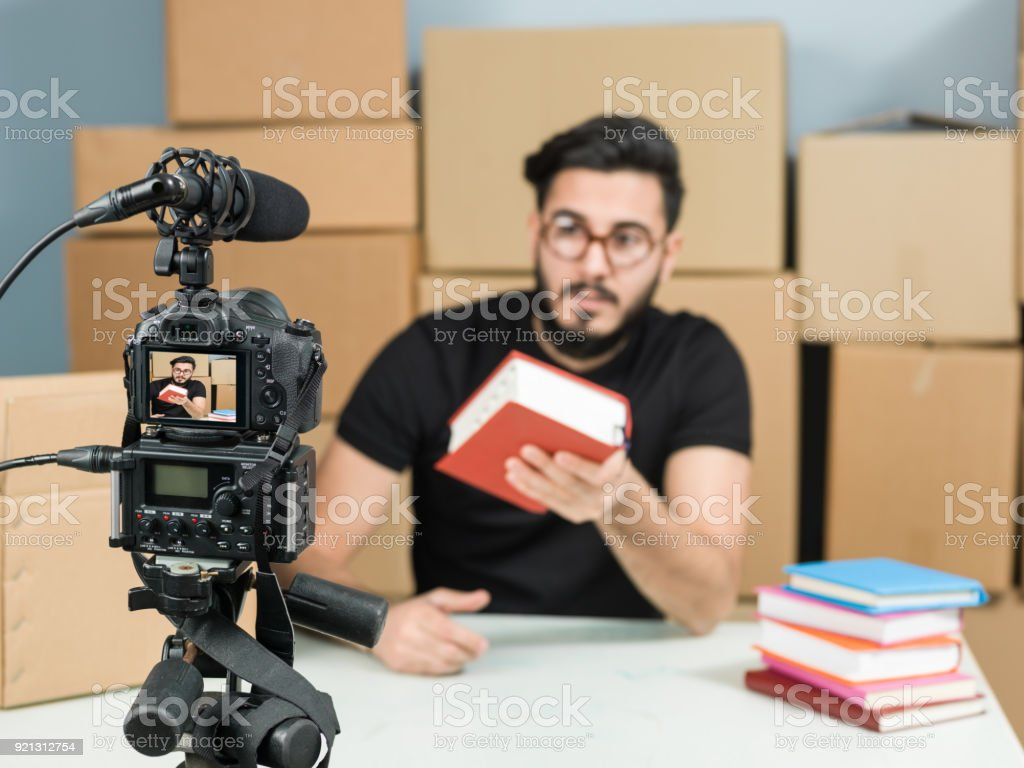 Adult Vlogger Man Recording Video Of Book Review For Video Blogging stock photo