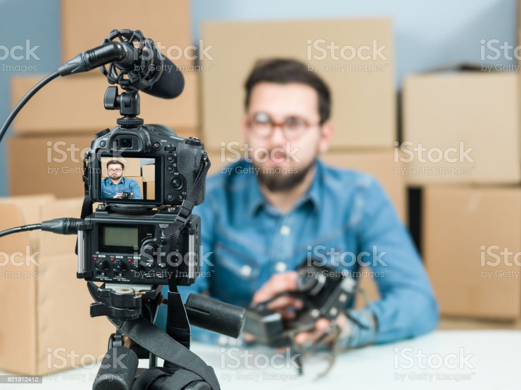 Adult Vlogger Man Recording Video Of Unboxing Camera For Video Blogging stock photo