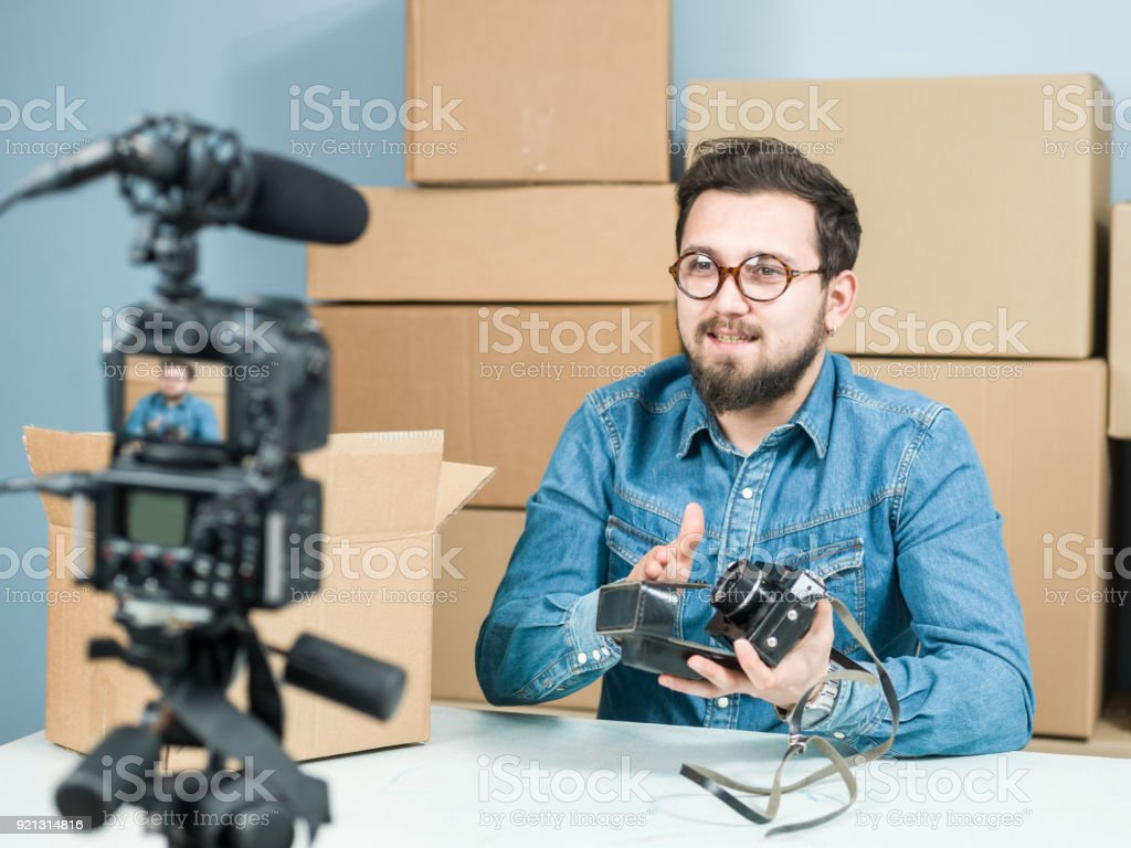 Adult Vlogger Man Recording Video Of Unboxing Camera For Video Blogging -  Stock image .
