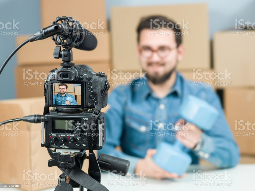 Adult Vlogger Man Recording Video Of Unboxing Sport Items For Video  Blogging - Stock image .