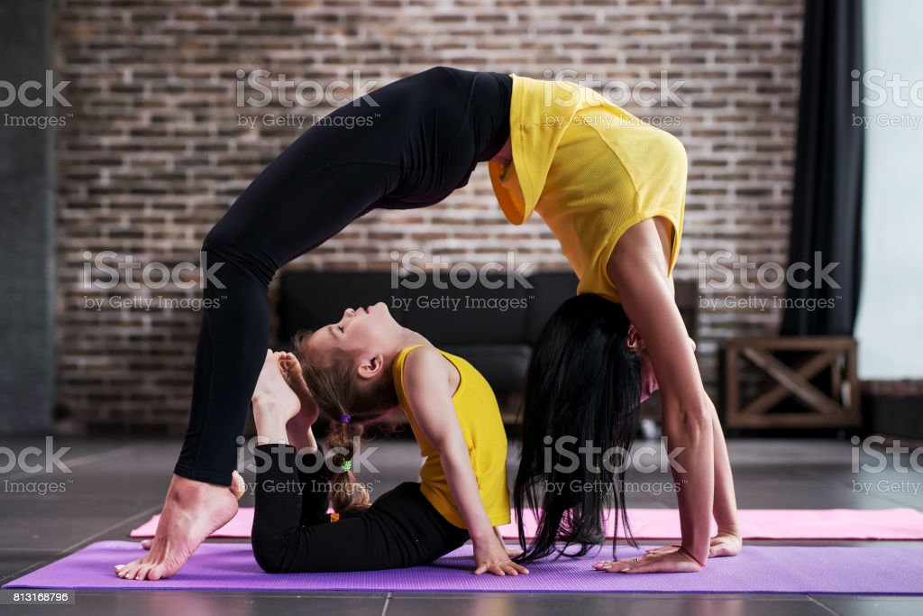 Adult woman and child girl practicing yoga together at home, adult standing in bridge pose and kid doing king cobra posture at home. stock photo