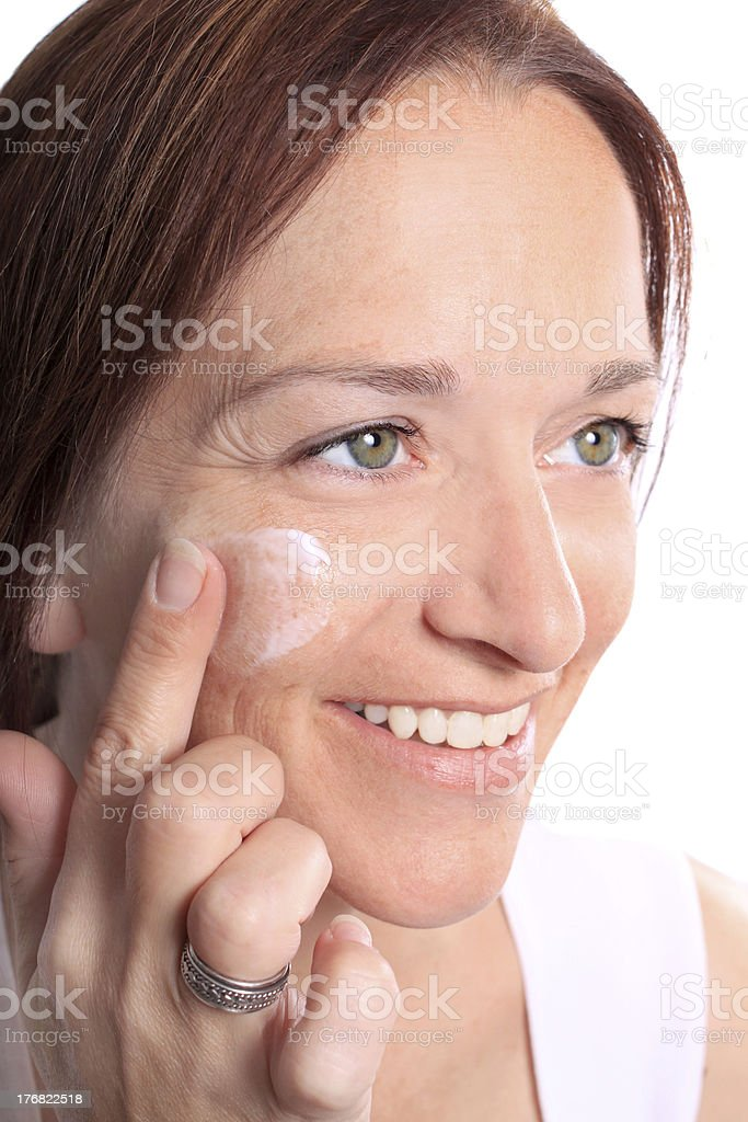 Adult woman applies cream on face royalty-free stock photo