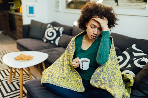 Adult African American woman staying at home feeling sick, having a headache and drinking a cup of tea