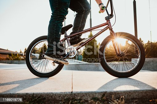 A mid-adult woman rides her BMX bicycle at a skateboard park on an early morning in Seattle, Washington, USA.