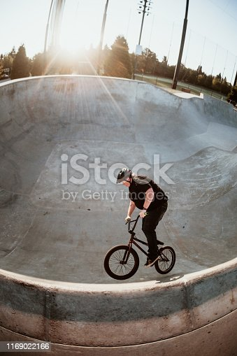 A mid-adult woman rides her BMX bicycle at a skateboard park on an early morning in Seattle, Washington, USA.  She gets airborne carving a large bowl / halfpipe.